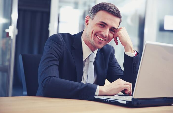 Cheerful businessman sitting with laptop at office.jpeg